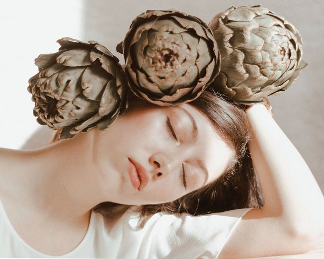 Close-up of beautiful woman with artichokes
