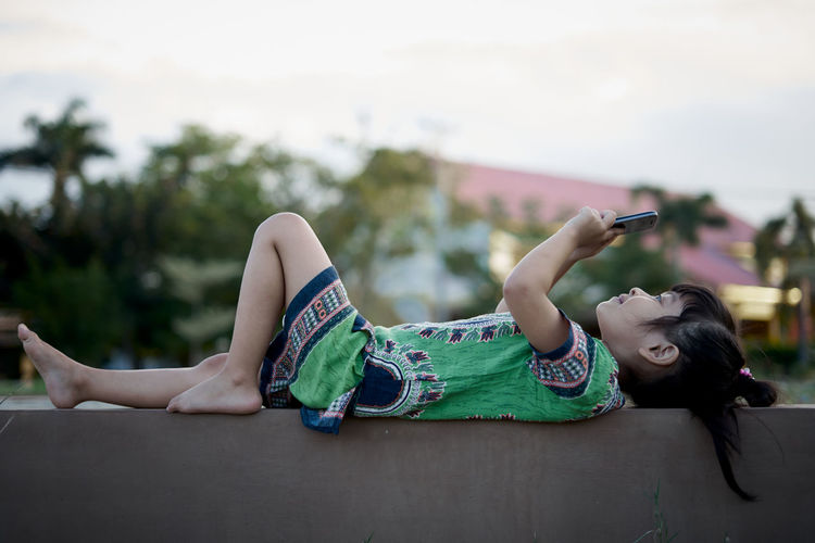 Girl using mobile phone while lying outdoors