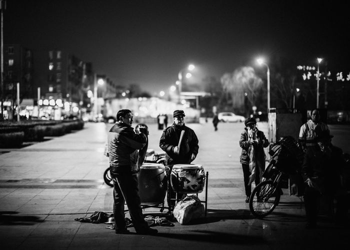 Rear view of people riding motorcycle on street at night