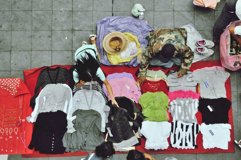 High Angle View Of Vendors Arranging Cloths On Sidewalk