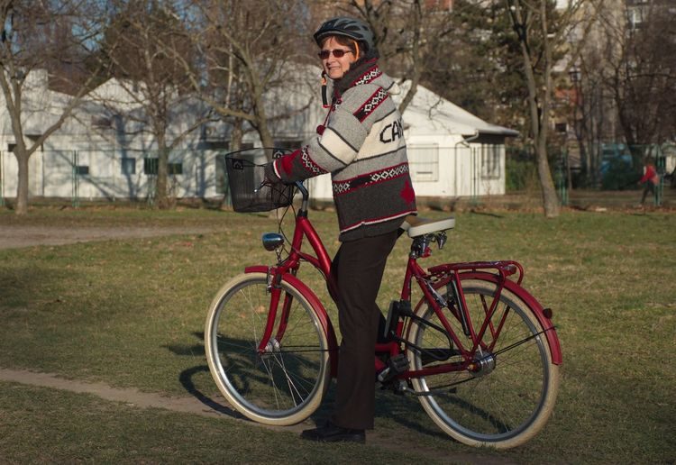 Bicycle One Person Transportation Tree Full Length Plant Portrait Adult Activity Day Focus On Foreground Sport Clothing Smiling Riding Outdoors Red Grass Green Field Path Helmet Warm Clothing