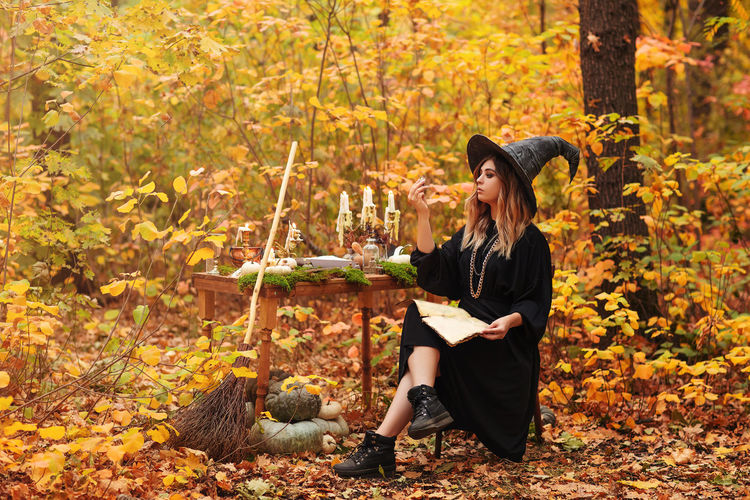 Young woman sitting on leaves during autumn