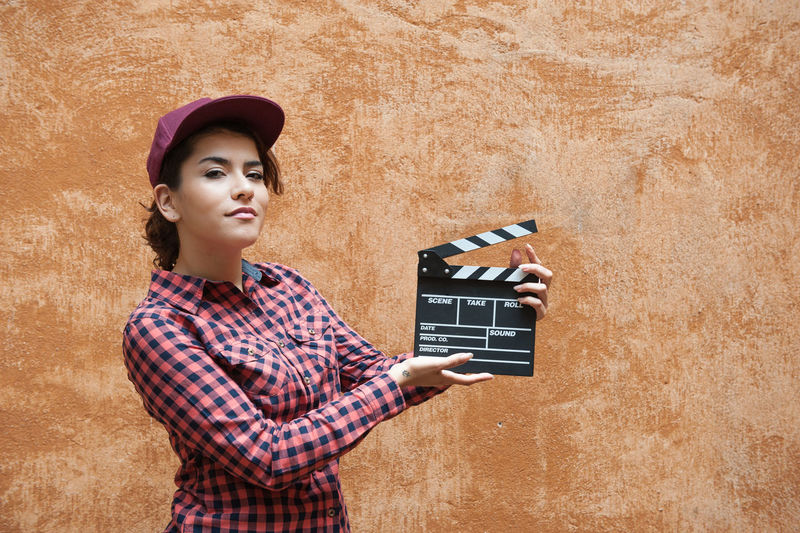 Portrait of young woman holding film slate against wall