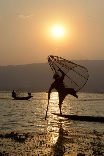 Silhouette men fishing in lake during sunset