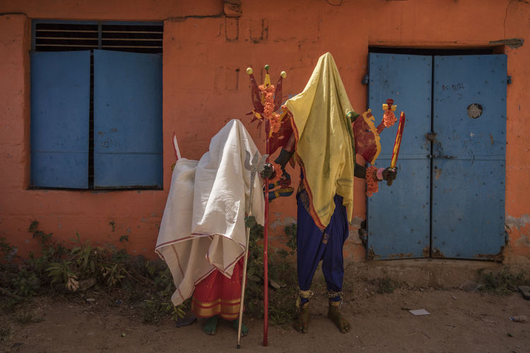 Artists in goddess costume covered in fabric against house during maha shivaratri