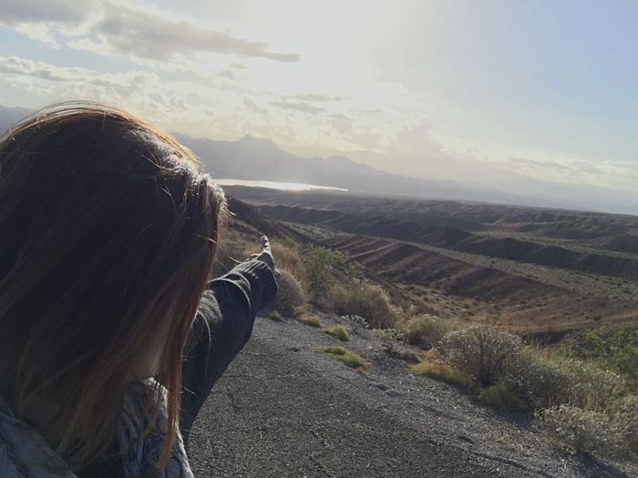 Close-Up Of Woman Pointing At Landscape Against Sky