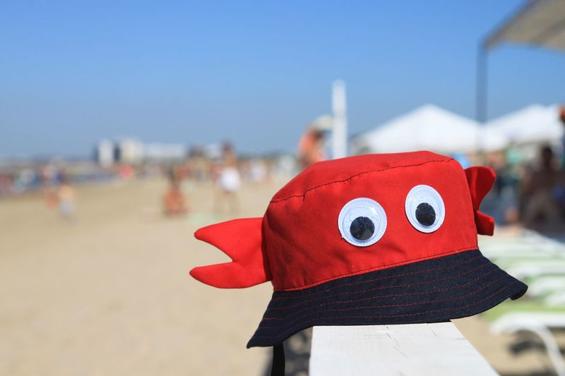 Close-up of red umbrella on beach against sky