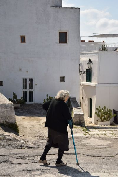 Colors Historical Building Puglia Travel Adult Architecture Building Building Exterior Built Structure Casual Clothing City Day Full Length Italy Lifestyles Nature One Person Outdoors Real People Rear View Scenics Senior Adult Senior Women Sunlight Travel Destinations Walking Walking Cane White Color Women