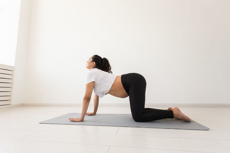 Woman sitting on floor against wall