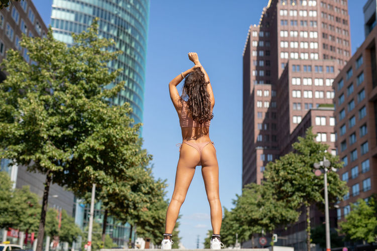 Young woman wearing bikini while standing against buildings in city