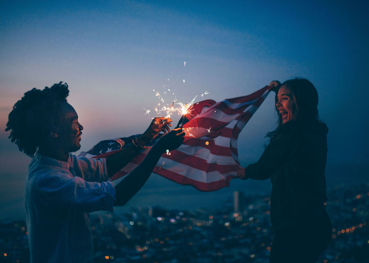 Side View Of Mid Adult Man Burning Sparklers While Girlfriend Holding American Flag Against Sky At Night
