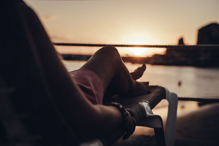 Low section of woman relaxing on lounge chair during sunset