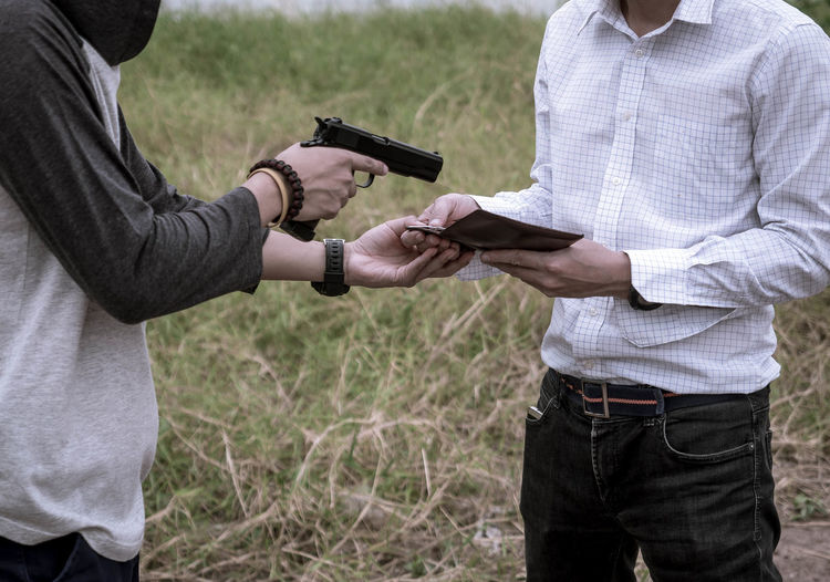 Midsection of criminal pointing gun at man while standing on field