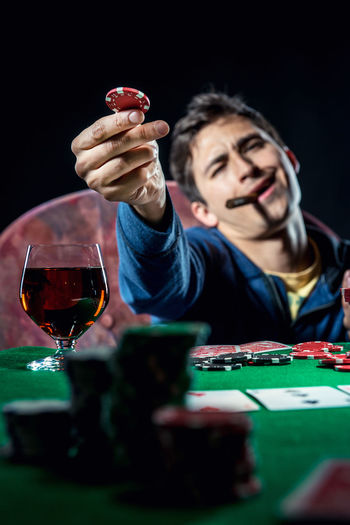Man Playing Poker With Whiskey And Cigar Against Black Background
