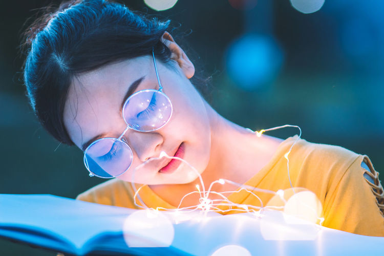 Close-Up Of Young Woman With Illuminated String Lights On Book