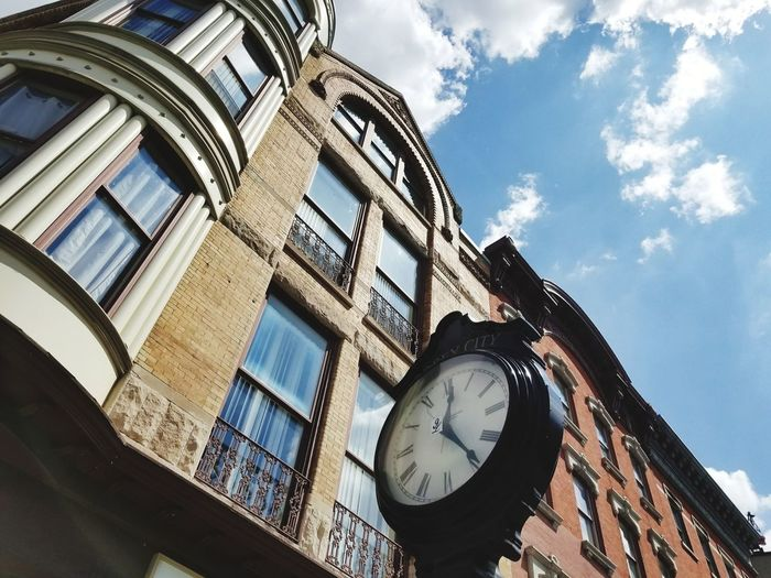Low angle view of clock against buildings in city