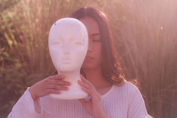 Woman with closed eyes holding statue outdoors