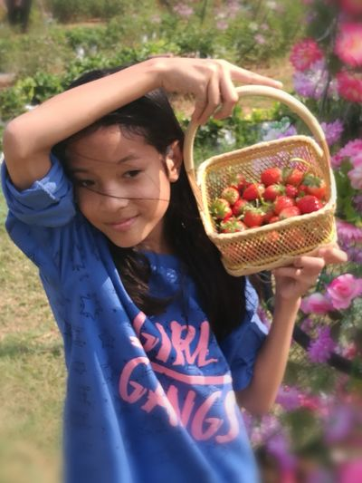 Smiling Girl Carrying Strawberry Basket