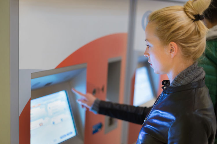 Side view of woman standing by vending machine at station