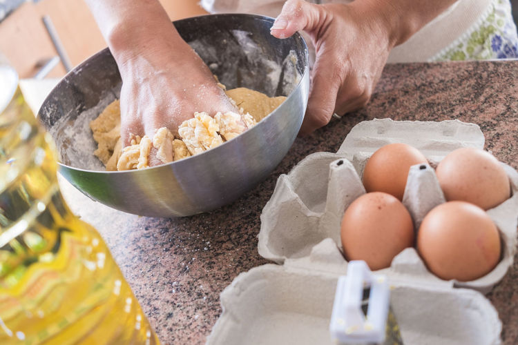 High angle view of woman kneading dough in bowl on kitchen counter