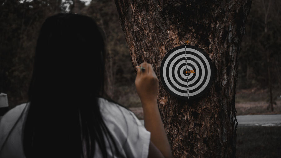 Rear view of woman holding dart against target on tree trunk in forest