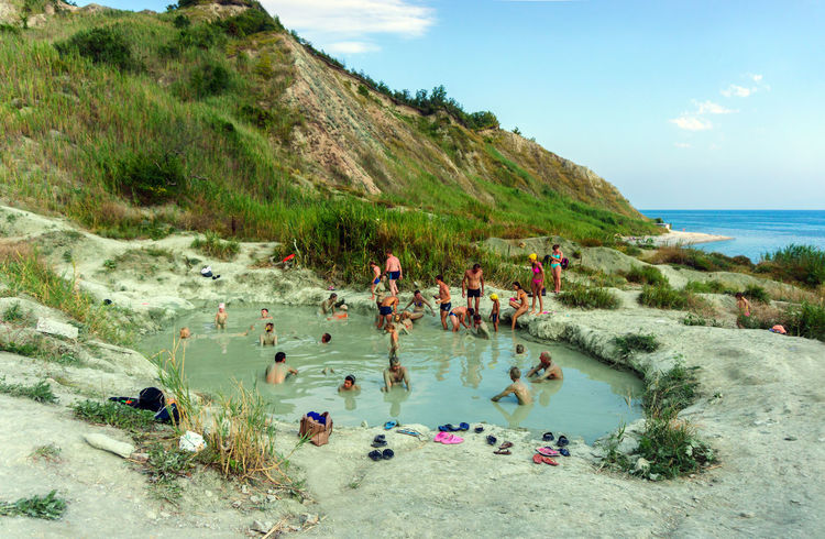 The people taking mud baths from blue clay Outdoor People Beauty In Nature Summer Muddy Waters Mud Bath Blue Sky Blue Clay Bath Nature Landscape Scenics Beach Water Seascape Clouds Seaside Cloudscape Sky Cloud - Sky Party - Social Event Large Group Of People Day Vacations Sun