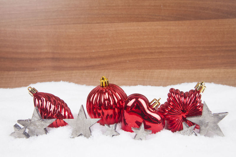 High Angle View Of Red Baubles With Star Shape Decoration On Snow