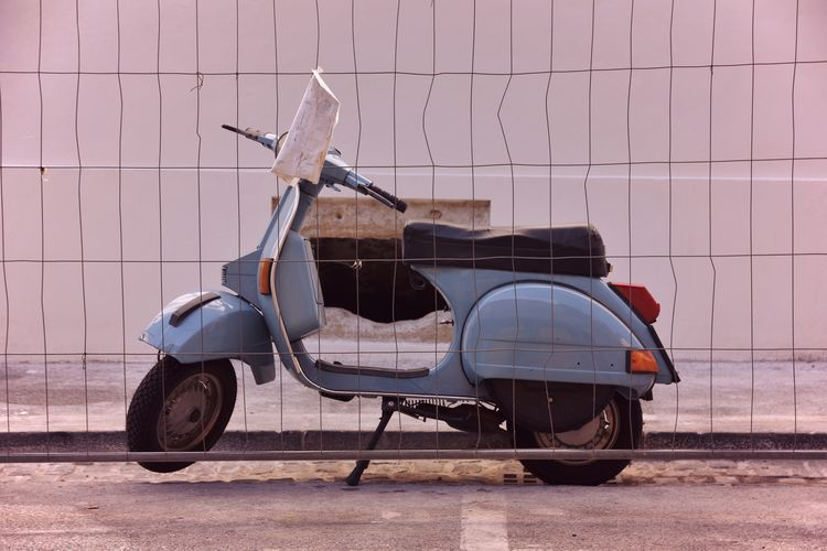 Side view of motorcycle on street against wall