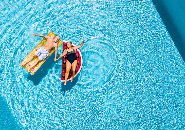 High angle view of women floating on swimming pool