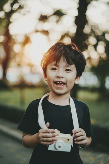 Portrait Of Happy Boy With Toy Camera Standing At Park During Sunset