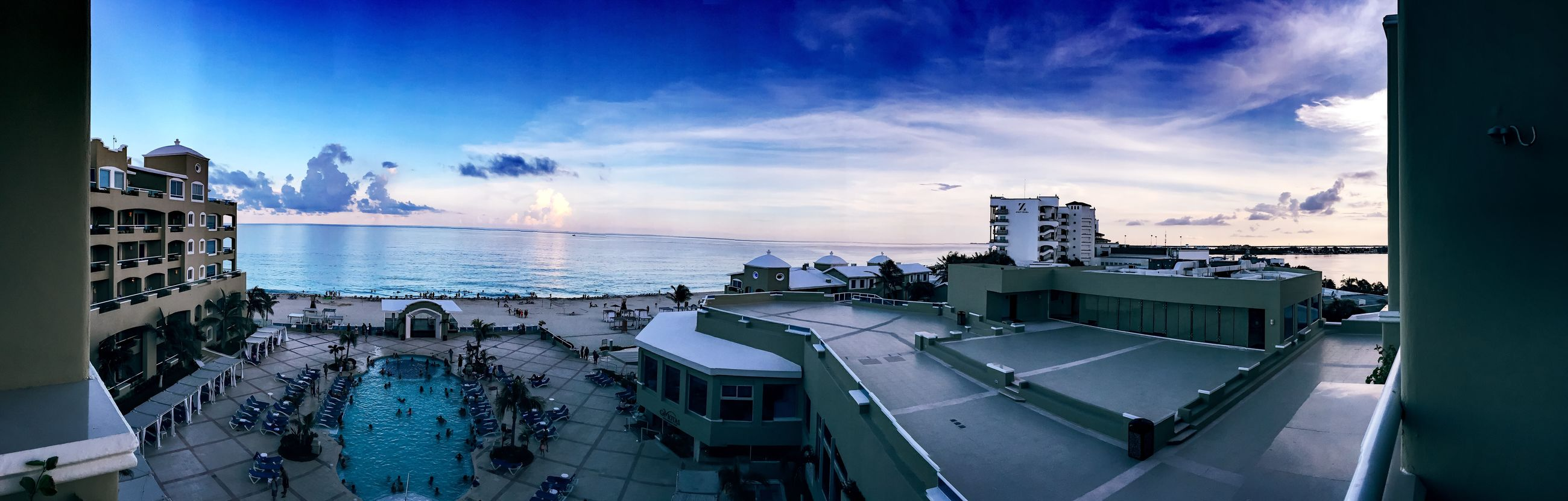 sky, building exterior, architecture, sea, built structure, blue, water, horizon over water, cloud - sky, panoramic, sunlight, city, cloud, outdoors, no people, auto post production filter, nature, residential structure, day, sunset