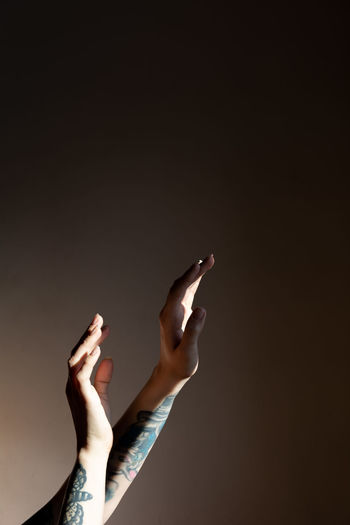 Low angle view of woman hand against black background