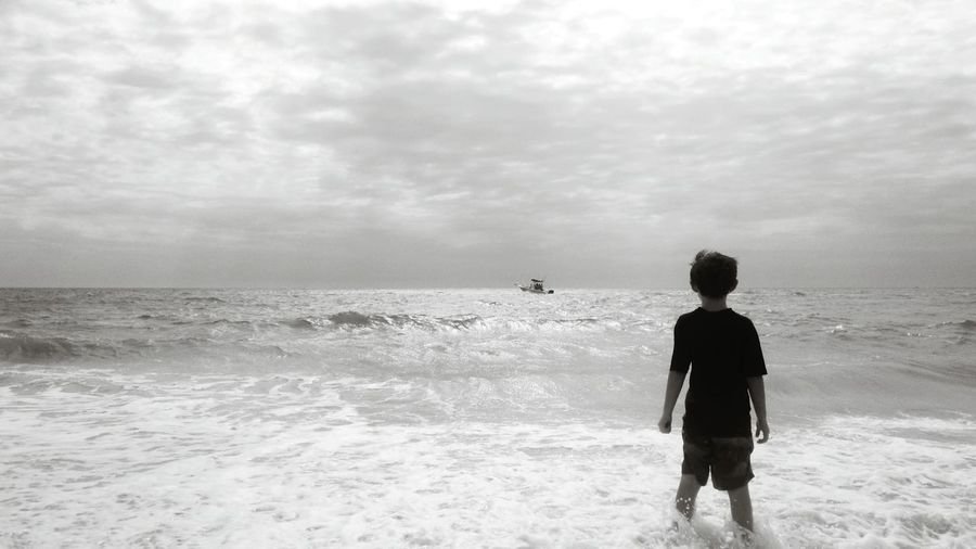 Rear view of boy standing at sea shore against cloudy sky