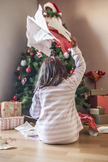 Rear view of girl unwrapping christmas present at home