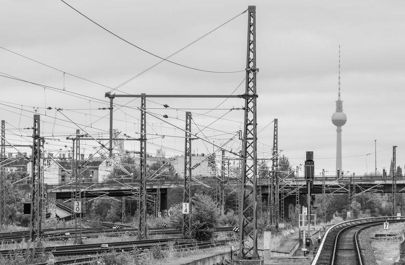 Electricity Pylon By Railroad Tracks Against Sky