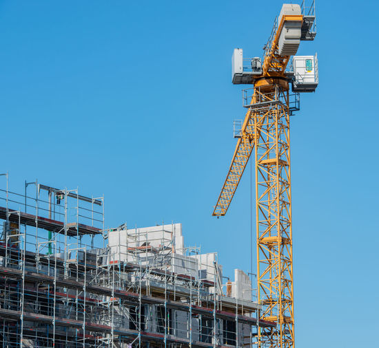 Low angle view of crane by incomplete building against clear blue sky