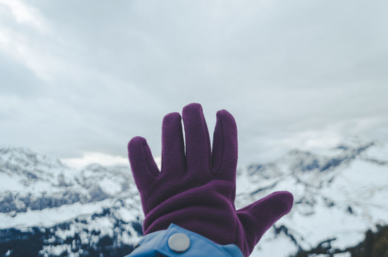 Person hand on snowcapped mountain against sky