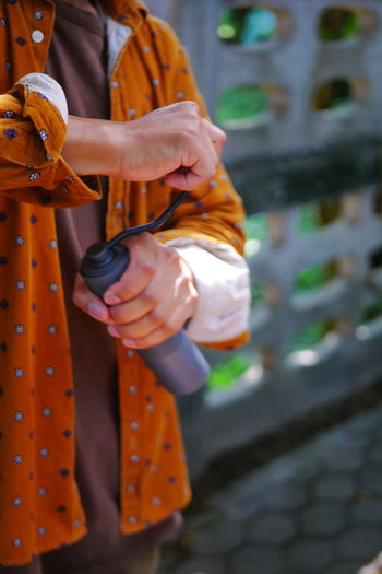 Midsection of woman holding orange while standing outdoors