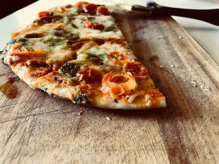 High angle view of pizza slice on wooden table