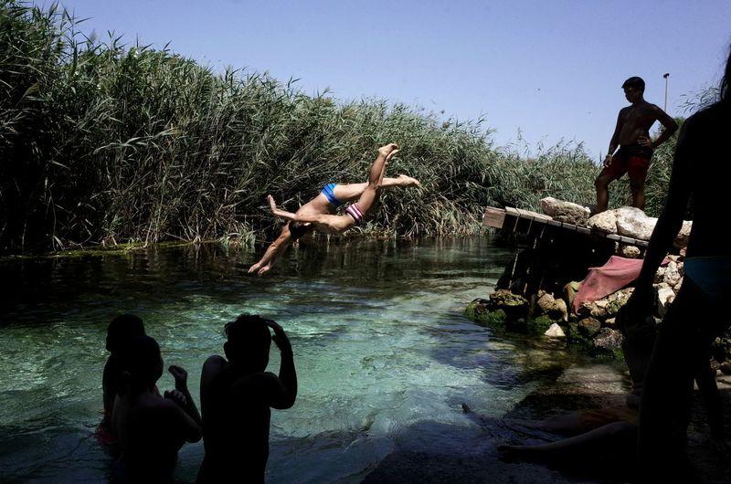 Men jumping in water against sky