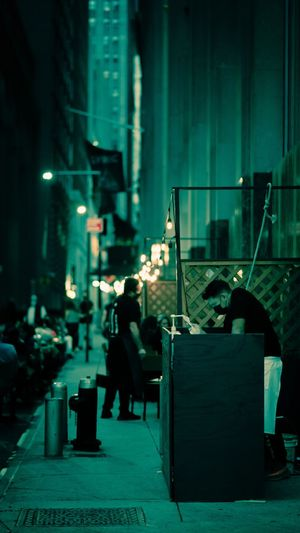 Man sitting on illuminated street against building at night