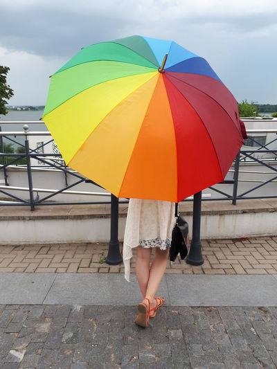 Rear view of woman with umbrella standing on footpath