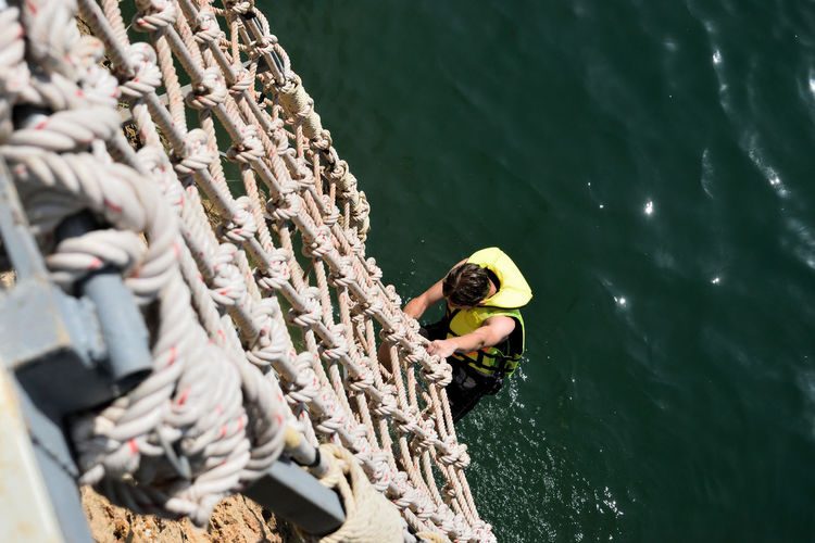 High angle view of man climbing ropes over lake