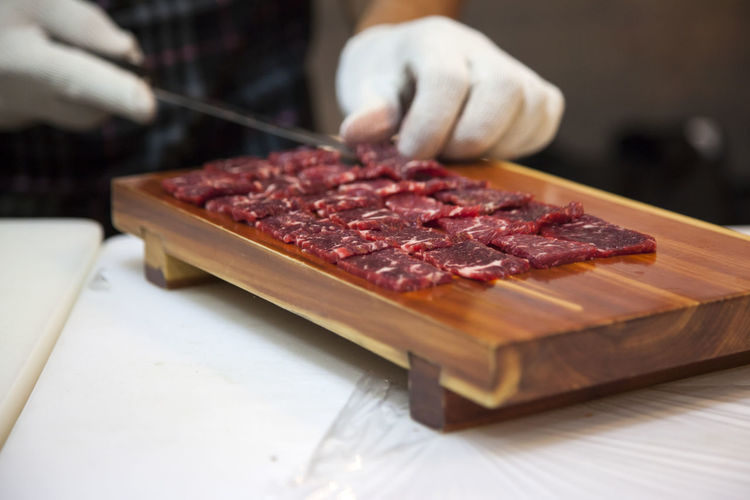 Close-Up Of Chef Preparing Beef Sashimi