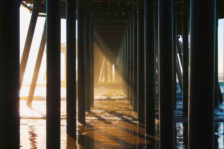Underneath view of pier at beach during sunset
