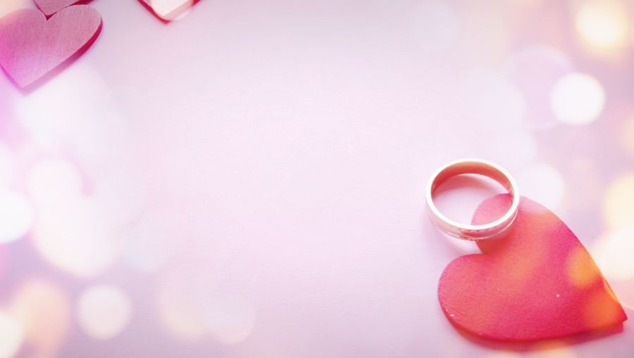 Close-up of wedding ring with red heart shapes over pink background