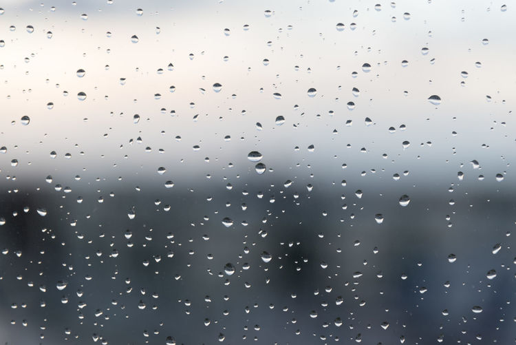 Rain drops on a wet window glass in a dark rainy day. Background behind completly blurred. Backgrounds Close-up Day Drop Full Frame Indoors  Nature No People RainDrop Sky Water Wet