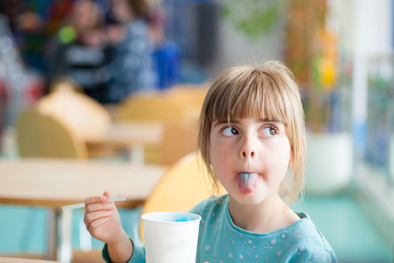 Cute blonde girl sticking or poking tongue out with blue crushed ice drink in brightly lit natural light cafe or restaurant Blond Hair Child Childhood Close-up Cool Kids Day Eating Elementary Age EyeEm Best Shots EyeEm Gallery Eyeem People Female Flavored Ice Food Food And Drink Freshness Frozen Food Girls Headshot Indoors  One Person Portrait Portraits Real People Sweet Food The Portraitist - 2018 EyeEm Awards
