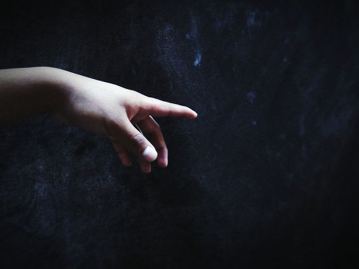 Close-up of hand gesturing towards wall