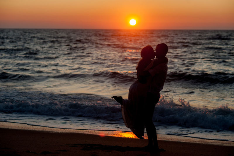 Side view of silhouette man kissing woman at beach against sky during sunset